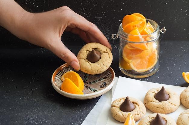 Kekse mit schokoladensüßigkeit in scheiben geschnittenen orangenstücken hand hält süße wüste