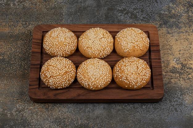 Kekse mit sesam auf einem holzteller.