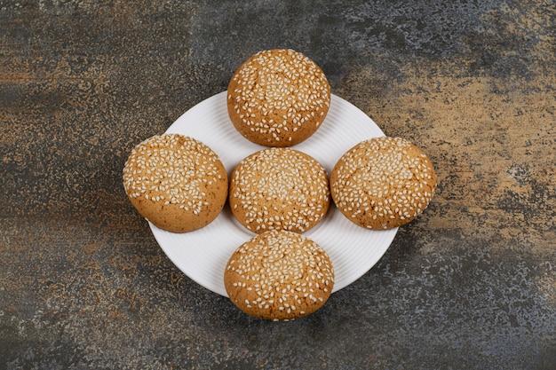 Kekse mit sesam auf weißem teller.