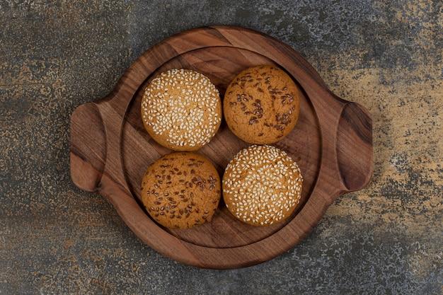 Kekse mit sesam und schokoladenstücken auf holzbrett.