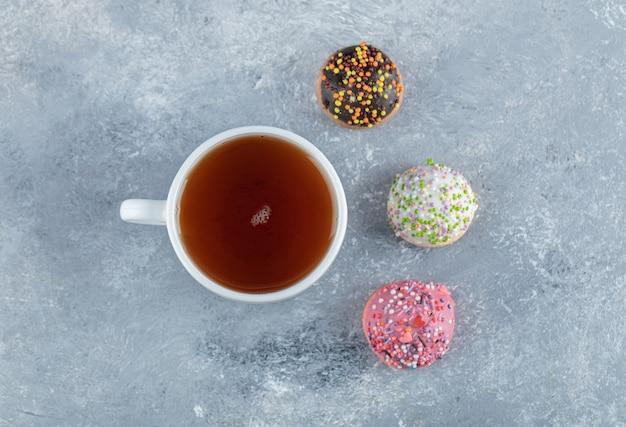Kekse mit streuseln und tasse tee auf marmortisch.