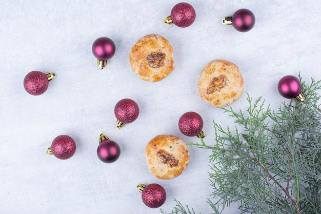 Kekse mit walnüssen und glitzernden weihnachtskugeln.