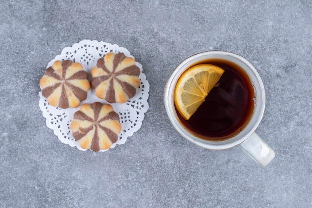 Kekse mit zebramuster und eine tasse tee auf marmoroberfläche