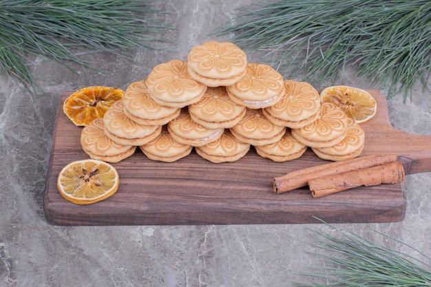 Kekse mit zimtstangen und trockenen zitronenscheiben auf einem holzbrett