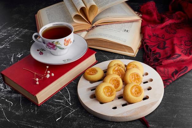Kekse mit zitrusfruchtmarmelade und einer tasse tee.