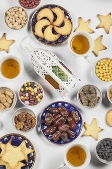 Kekse nüsse und datteln auf dem weißen tisch