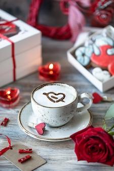 Kekse oder lebkuchen in einer geschenkbox mit einem roten band auf einem holztisch. valentinstag.