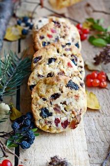 Kekse shortbread kekse mit getrockneten früchten getrocknete cranberries rosinen getrocknete aprikosen pflaumen und nüsse auf einem hölzernen hintergrund