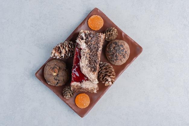 Kekse, tannenzapfen, gummibärchen und ein stück kuchen auf einer platte auf marmoroberfläche