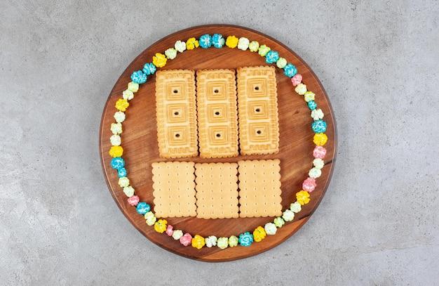 Kekse umgeben von bonbons in einem kreis auf holzbrett auf marmorhintergrund. hochwertiges foto
