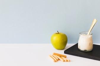 Kekse und Apfel nahe Jogurt und Notizbuch