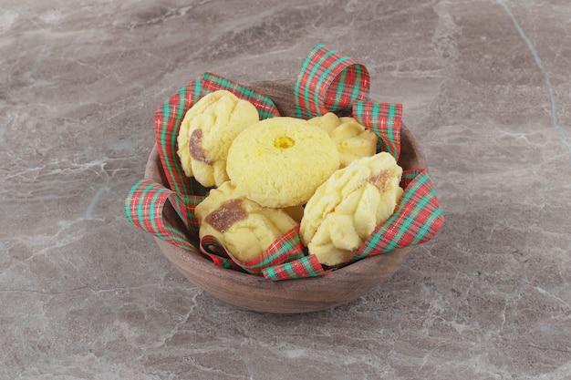 Kekse und bänder in einer kleinen schüssel auf marmor