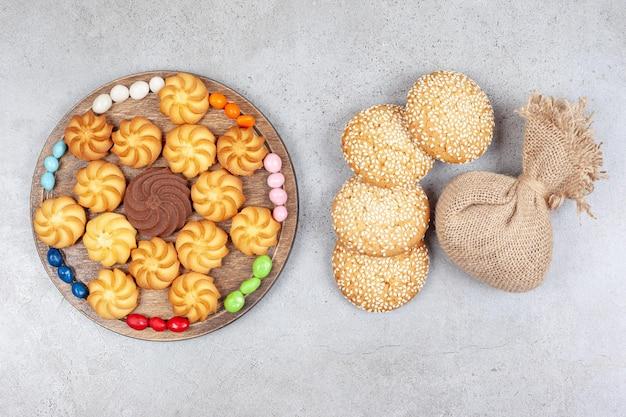 Kekse und bonbons auf holzbrett neben keksen und einem sack auf marmorhintergrund. hochwertiges foto