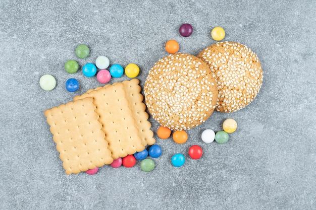 Kekse und bunte bonbons auf marmoroberfläche
