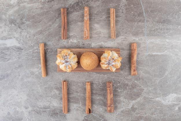 Kekse und ein cupcake auf einem kleinen servierbrett, umgeben von zimtstangen auf marmoroberfläche