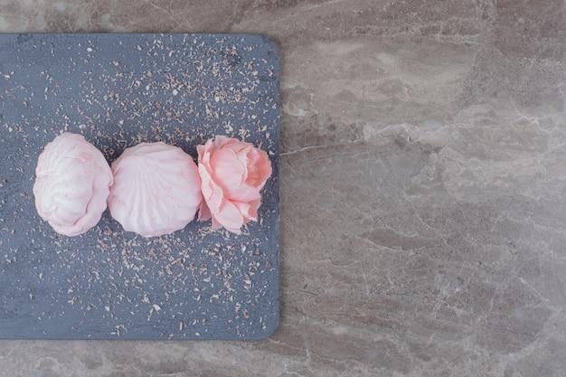 Kekse und eine blumenkrone auf einem brett auf marmor