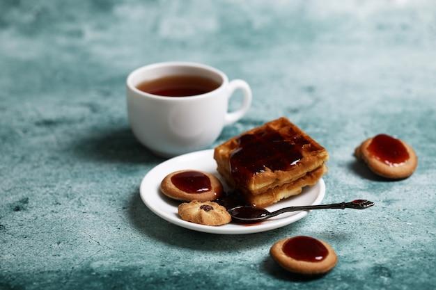 Kekse und eine weiße tasse tee.