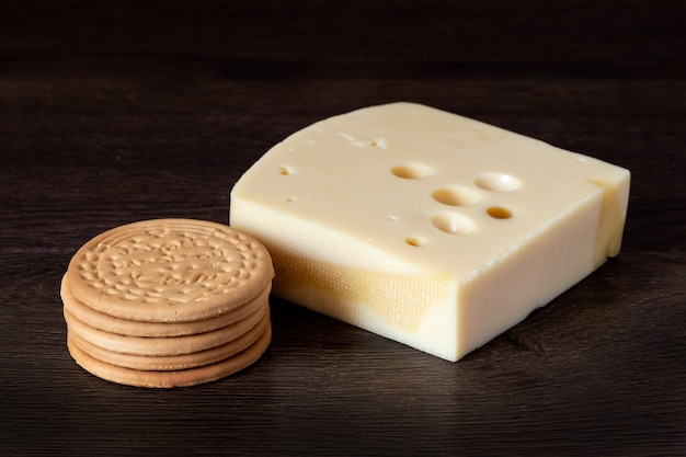 Kekse und fester frischkäse auf dunklem holzhintergrund. leckeres und gesundes essen