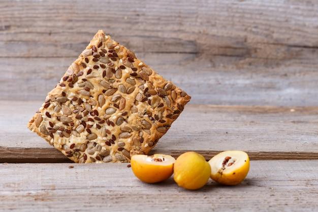 Kekse und gelbe quitte tragen auf einem hölzernen hintergrund früchte