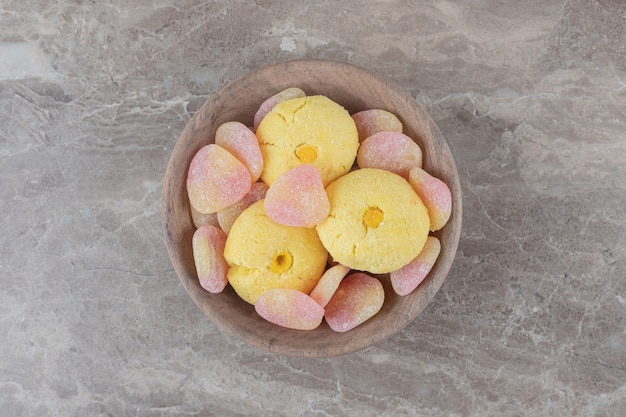 Kekse und geleebonbons gebündelt in einer kleinen schüssel auf marmoroberfläche