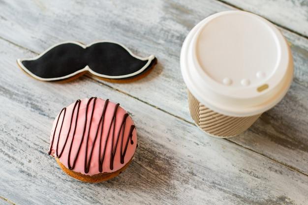 Kekse und heißgetränkebecher. glasierter keks in form eines schnurrbartes. frischer kaffee und gebäck. morgendessert eines herrn.