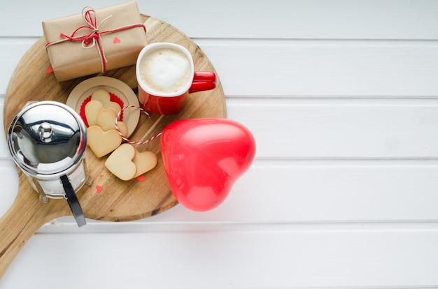 Kekse und herzförmiger ballon, kaffeetasse und umwickelte schachtel