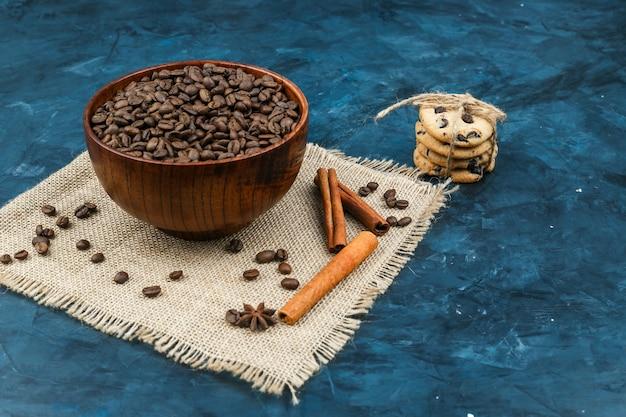 Kekse und kaffeebohnen auf einem dunkelblauen hintergrund