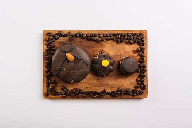 Kekse und kaffeebohnen auf schneidebrett