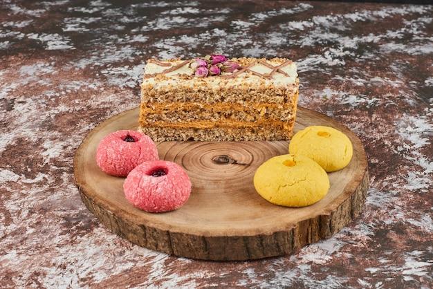 Kekse und karottenkuchen auf einem holzbrett.