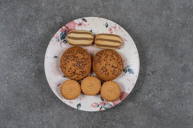 Kekse und kekse auf dem teller auf der marmoroberfläche