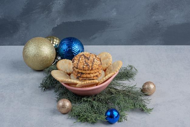 Kekse und kekse in einer schüssel inmitten von weihnachtsschmuck auf marmoroberfläche