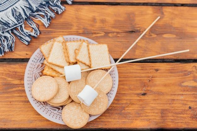 Kekse und marshmallows zum braten am stäbchen smores