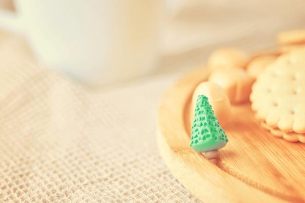Kekse und süßigkeiten auf einem holztablett ein kleiner grüner weihnachtsbaum aus plastilin-schokoladenbonbons ...