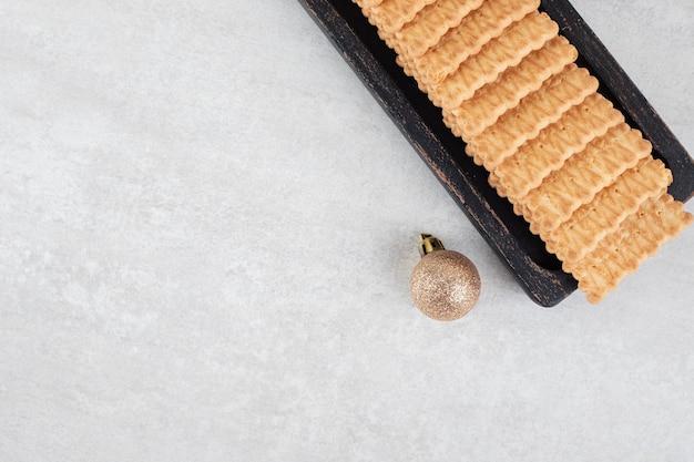 Kekse und weihnachtskugel auf marmoroberfläche