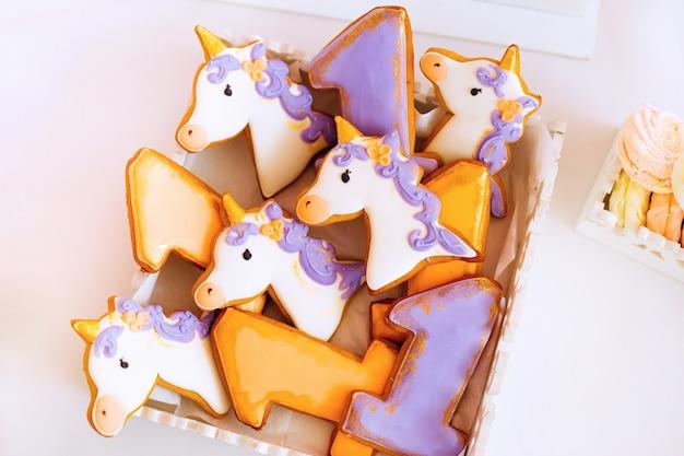 Kekse von lila und gelb in form eines einhorns und nummer eins