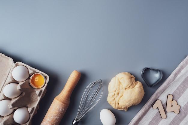 Kekse zum valentinstag machen, flach legen, draufsicht, platz kopieren. verschiedene zutaten, nudelholz, teig, eier, nummern 14, schneebesen auf grauem hintergrund, layout auf grauem hintergrund.