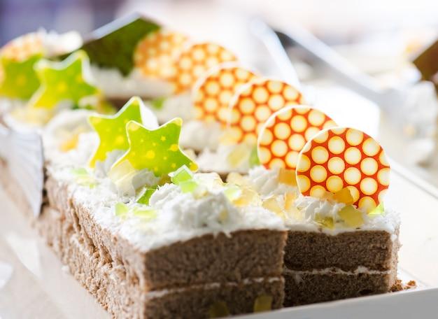 Kekskuchen, dekoriert mit sahne und weißer schokolade auf einem weißen teller.
