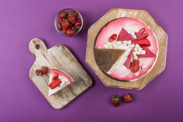 Kekskuchen mit erdbeerfüllung und frischen erdbeeren mit einem geschnittenen stück auf einem holzständer