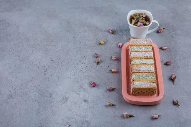 Kekssandwich gefüllt mit bunter marmelade auf rosa teller und tasse tee.