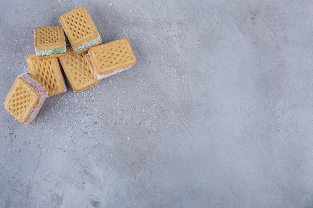 Kekssandwich gefüllt mit bunter marmelade auf stein.