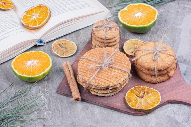 Kekssorten auf einem holzbrett mit zimt und orangen