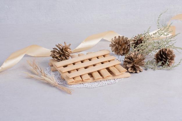 Keksstäbchen mit tannenzapfen auf weißem tisch