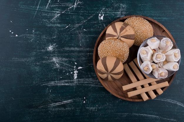 Keksteller mit brötchen, lokum und waffelstangen, draufsicht