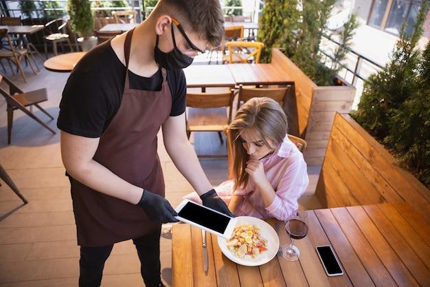 Kellner arbeitet in einem restaurant in einer medizinischen maske, handschuhe während der coronavirus-pandemie