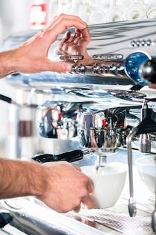 Kellner bereitet espresso an einer automatischen kaffeemaschine zu