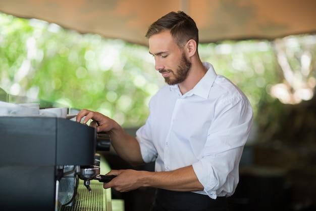 Kellner bereitet espresso im restaurant zu