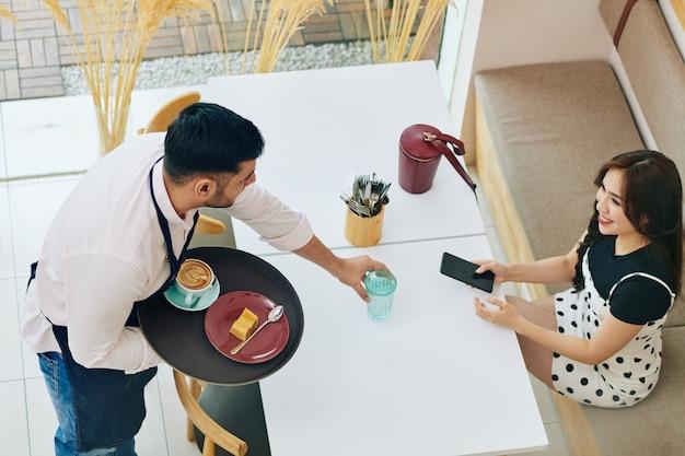 Kellner bringt bestellung zum kunden