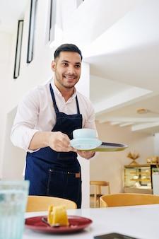 Kellner bringt cappuccino und kuchen
