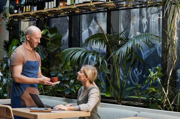 Kellner bringt die tasse kaffee zu der geschäftsfrau, die am tisch sitzt und im café am laptop arbeitet