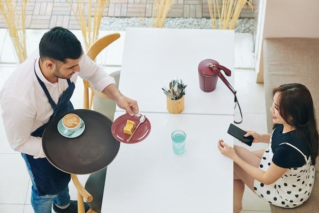 Kellner bringt ein stück köstlichen kuchens und eine tasse cappuccino zu hübscher junger frau am kaffeetisch